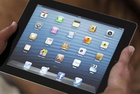 An illustration picture show sapplication icons are displayed on an Apple Ipad tablet held by a woman in Bordeaux